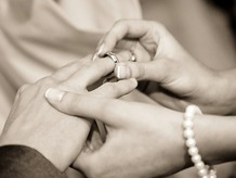 Ring being placed on a finger at a wedding